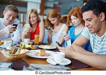 Modern people - Friends sitting at café absorbed in their...
