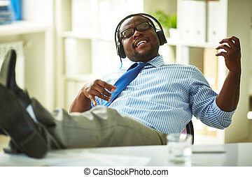Distraction - Businessman sitting in headphones in office
