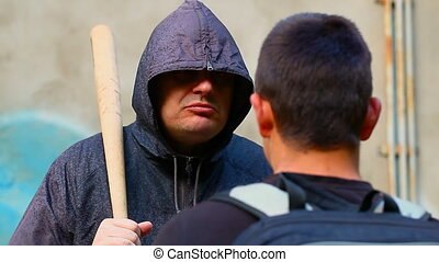 Man with a baseball bat against teenager at outdoor