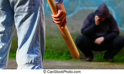 Aggressive teenager with a baseball bat against man with...