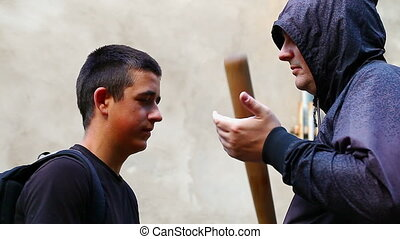 Man with a baseball bat against teenager near wall