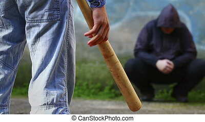 Aggressive teenager with a baseball bat against man at...