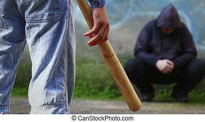 Aggressive teenager with a baseball bat against man at...