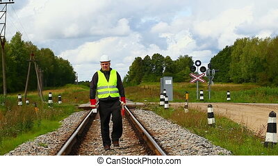 Railroad maintenance worker with showel on the railway