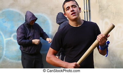 Aggressive teenager with a baseball bat with two mens behind...