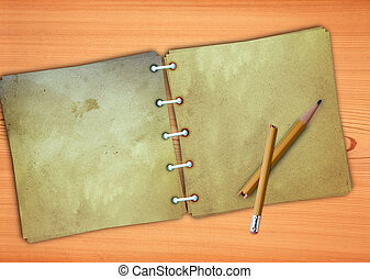 Old memo pad and a broken pencil on a wooden background.