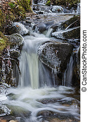 Small waterfall with icicles and ice close up, spring.