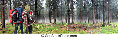 Couple hiking through misty forest - Young couple, wearing...