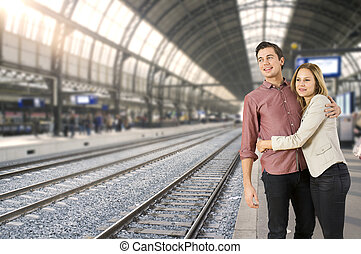 Train station couple - Young couple hugging each other on a...