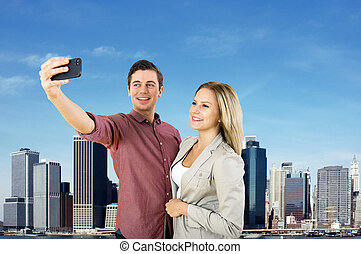 Skyline Selfie - Young urban couple taking a selfie in front...
