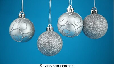 Four silvery  Christmas balls on a blue background