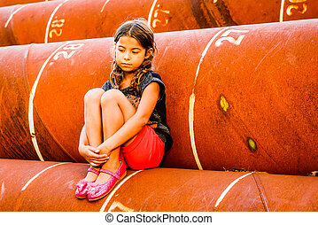 Little girl sitting on the pipes