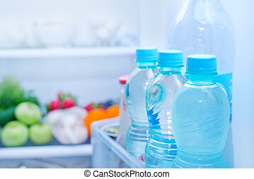 Refrigerator full of food, water in bottles
