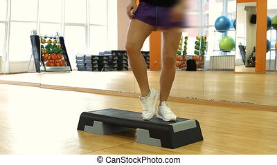 Beautifull female legs on the step board during exercise