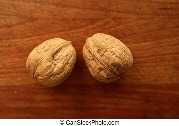 Two walnuts on a golden wood table