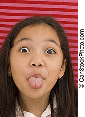 Asian Girl Sticking Tongue Out Against Striped Background.