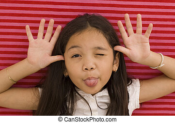 Asian Girl Making Face Against Paper Background.