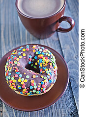 chocolate donuts and coffee in cup on a table