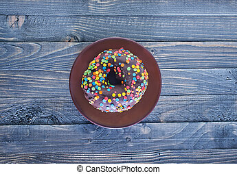 chocolate donut on plate and on a table