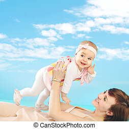 Attractive mom holding her tiny daughter - Attractive mother...