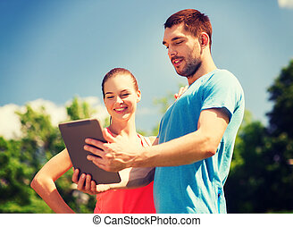 smiling couple with tablet pc outdoors - fitness, sport,...