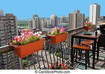 Rooftop patio with table and stool chairs, colorful flower...