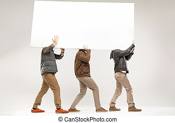 Conceptual picture of three guys carrying the board -...
