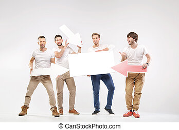 Group of joyful guys holding symbols - Group of joyful guys...