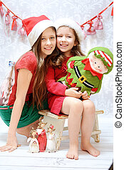Two smiling sisters wearing santa hats - Two young sisters...