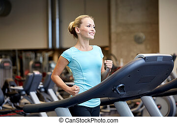 smiling woman exercising on treadmill in gym - sport,...