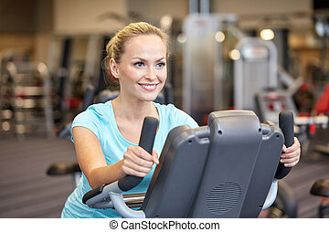 smiling woman exercising on exercise bike in gym - sport,...