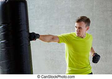 young man in gloves boxing with punching bag
