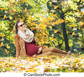 Smiling lady watching flying leaves
