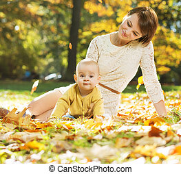 Mom lying on the leaves with baby