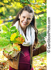 Pretty mother holding bouquet of leaves