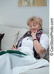 Doing crossword - Elderly smart woman doing crossword