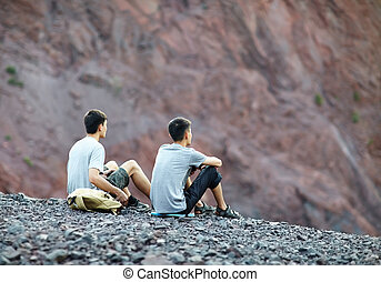 Two young men sitting on rocky cliff - Two tourist young men...