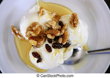 Greek yogurt dessert with honey and walnuts nuts over white...