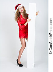 Naughty girl in red dress and santa hat with blank white...