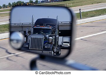 A big blue truck in the vehicle mirror