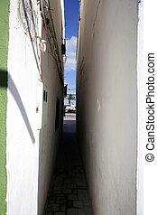 Extremely narrow street, white walls, blue sky,...