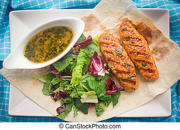 fish cakes with salad and sauce on pita bread