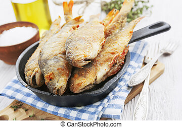 Fried fish in a frying pan on the table