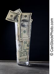 High glass full of dollar notes over black background