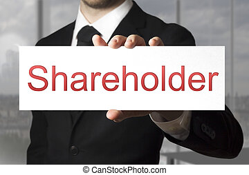 businessman holding sign shareholder - businessman in black...