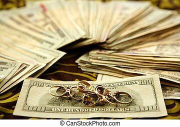 Dollar notes and gold rings over tablecloth, studio...