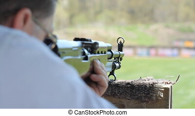Practice at the rifle range. CU. - Over shoulder shot of man...