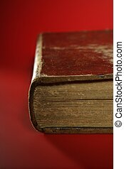 Old aged classic book close up over red background