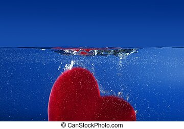 Candy red heart shape sinking into the blue water side view