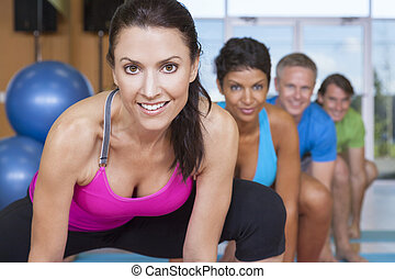 Interracial Group of Middle Aged People Practicing Yoga - An...
